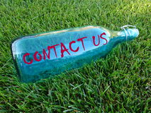 Contact us bottle. Blue glass bottle with text message contact us. Background  green grass Stock Images