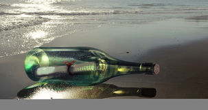 Message in a bottle. Glass bottle containing a message, on the beach Stock Image