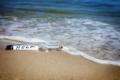 Message in a bottle / Help!. / deserted beach stock images