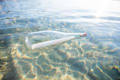 Message in a bottle. Floating in the sea. Glass bottle with help message in the water Stock Image