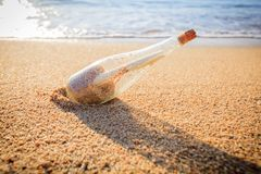 Message in a bottle. On sand beach at sunset. Help and communication Royalty Free Stock Photo