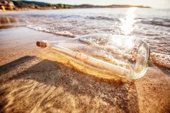 Message in a bottle. On sand beach at sunset. Help and communication Stock Photography