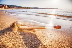 Message in a bottle. On sand beach at sunset. Help and communication Stock Image