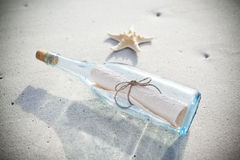 Message In A Bottle. A message in a bottle with a note inside on a beach. SOS- Save Our Souls Stock Images