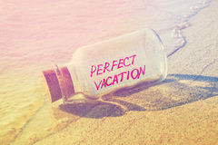 Message in a bottle Perfect vacation on sandy beach. Stock Photo