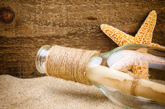 Message in the bottle. On rough wood background Royalty Free Stock Images