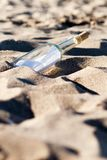 Message in a bottle in the sand stock images