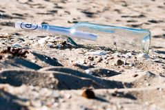 Message in a bottle in the sand. A message in a bottle with at-sign in the sand royalty free stock photos