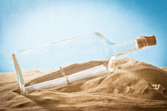 Message in bottle on sand. Glass bottle with a message of support within the bank stock images
