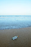 Message in a bottle in the sand of the beach. Bottle found on the beach with a message inside Royalty Free Stock Photos