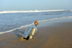 Message in a bottle in the sand of the beach. Bottle found on the beach with a message inside Royalty Free Stock Image