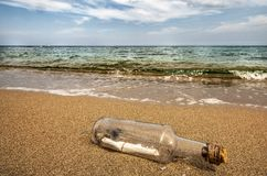 Message in a bottle in the sand of the beach stock illustration