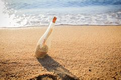 Message in a bottle. On sand beach at sunset. Help and communication Royalty Free Stock Photos