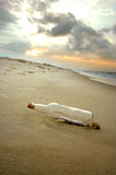 Message in a Bottle On Shore. Message in a bottle stranded on a deserted shore as the sun is setting stock images
