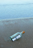 Message in a bottle on the shore of the beach. Bottle found on the beach with a message inside Stock Images