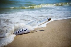 Message in a bottle / SOS!. / deserted beach Stock Photography
