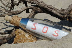 Message in a bottle with SOS signal. Buried in the sand royalty free stock photo