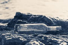 Message in a bottle on a stone covered with seaweed. Message in a corked bottle on a stone covered with seaweed royalty free stock image