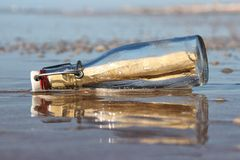 Message in a bottle. Stranded on the beach royalty free stock photos