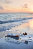 Message in a Bottle at Sunset. Message in a bottle on sandy shore at sunset royalty free stock images
