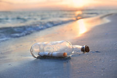 Message in a Bottle at Sunset. Message in a bottle resting on shore during sunset royalty free stock images