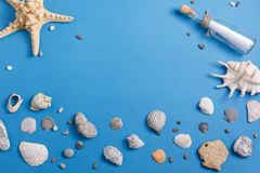 Message in a bottle on a turquoise background with seashells and starfish. View from above. stock photos