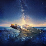 Message in a bottle. Under a beautiful night sky Royalty Free Stock Image