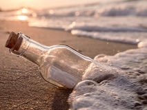 Message in the bottle. Washed ashore against the Sun setting down Royalty Free Stock Image