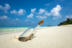 Message in a bottle washed ashore on tropical beach. Stock Image
