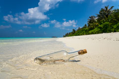 Message in a bottle washed ashore on a tropical beach Royalty Free Stock Photography