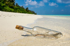 Message in a bottle washed ashore on a tropical beach Stock Image