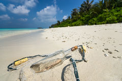 Message in a bottle washed ashore on a tropical beach. Stock Photography