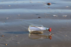 Message in bottle washed onto the sand royalty free stock photography