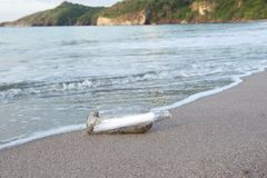 Message in bottle washed up lonely coastline Royalty Free Stock Photos