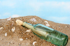 Message in a bottle washed up on a sandy shore Royalty Free Stock Images