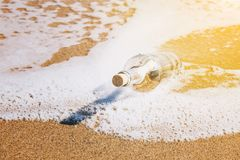 Message in a bottle washed up by the sea. Lying half submerged in the golden beach sand on the edge of the surf in a conceptual image of romance or a shipwreck Stock Photo