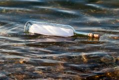 Message in a bottle in the water Royalty Free Stock Images