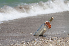 Message in a bottle with a wave coming Royalty Free Stock Images