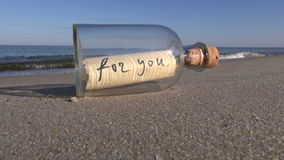 "Message in bottle with words ""for you"" on ocean beach"