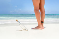 Message in a bottle. And young woman legs stock photography