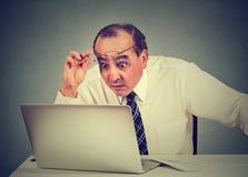 Message choqué de lecture d'homme sur l'ordinateur dans le bureau Images stock