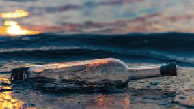Message in a corked bottle on coast, asking for help royalty free stock photography