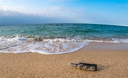 Message in a corked bottle on the empty beach stock photo