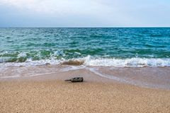 Message in a corked bottle on the empty beach. A message in a corked bottle on the empty beach royalty free stock photos