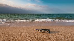 Message in a corked bottle on the empty beach. A message in a corked bottle on the empty beach stock images