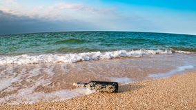 Message in a corked bottle on the empty beach. A message in a corked bottle on the empty beach royalty free stock photo