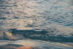 Message in a corked bottle on shore, hope of salvation stock photo