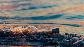 Message in a corked bottle on shore, hope of salvation royalty free stock images