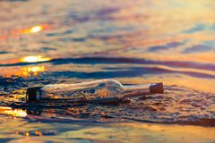 Message in a corked bottle on shore, hope of salvation stock images