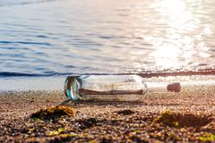 Message in a corked bottle on shore, hope of salvation royalty free stock photo
